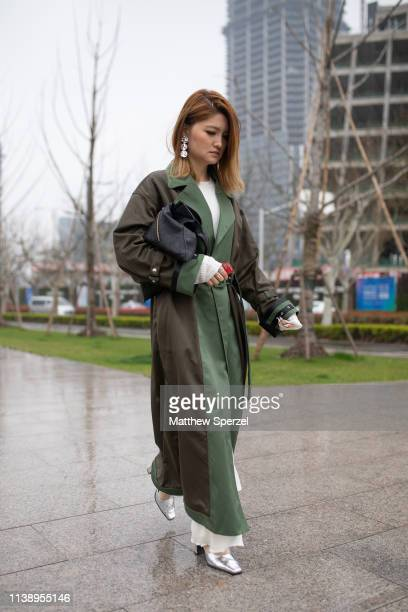 A guest is seen on the street attending Labelhood during Shanghai Fashion Week A/W 2019/2020 wearing moss and olive coat white sweater silver...