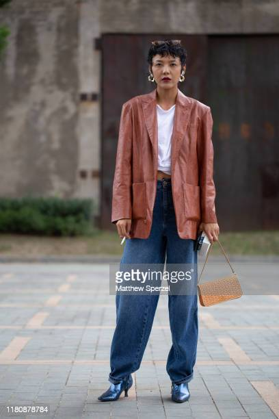 Guest is seen on the street attending Labelhood during Shanghai Fashion Week wearing brown leather jacket, white tshirt, baggy blue jeans, blue...