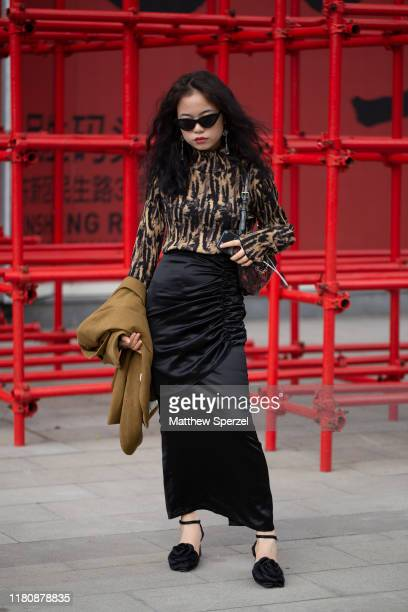 A guest is seen on the street attending Labelhood during Shanghai Fashion Week wearing black/gold pattern top black silk skirt copper blazer and...