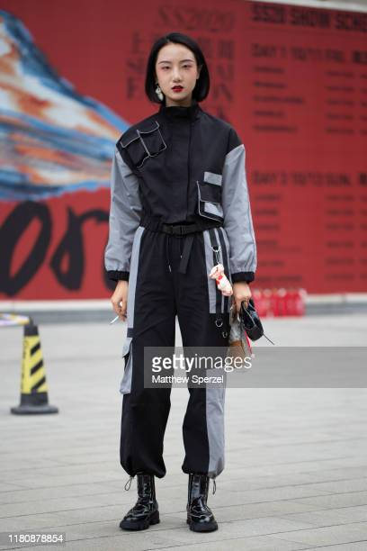 A guest is seen on the street attending Labelhood during Shanghai Fashion Week wearing Heliot Emil black/grey outfit with black boots on October 13...
