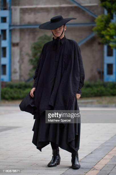 Guest is seen on the street attending Labelhood during Shanghai Fashion Week wearing all-black outfit with black wide brim hat and boots on October...