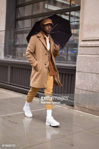 A guest is seen on the street attending Landlord during New York Fashion Week Men's wearing a camel coat and gold pants and cap on February 7 2018 in...