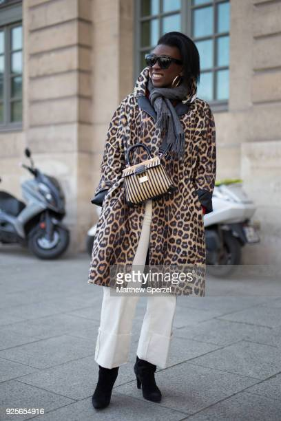 A guest is seen on the street attending Lanvin during Paris Fashion Week Women's A/W 2018 Collection wearing a leopard print coat with grey scarf on...