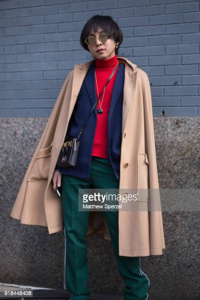 A guest is seen on the street attending Leanne Marshall during New York Fashion Week wearing a camel coat navy blazer red sweater adn green pants...