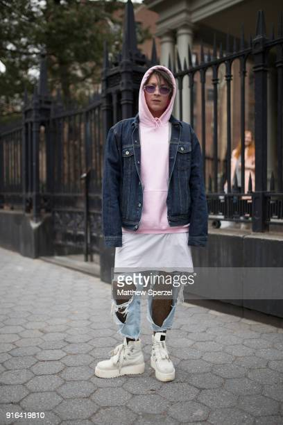 A guest is seen on the street attending Linder during New York Fashion Week wearing a pink hoodie navy denim jacket and torn blue jeans on February 9...