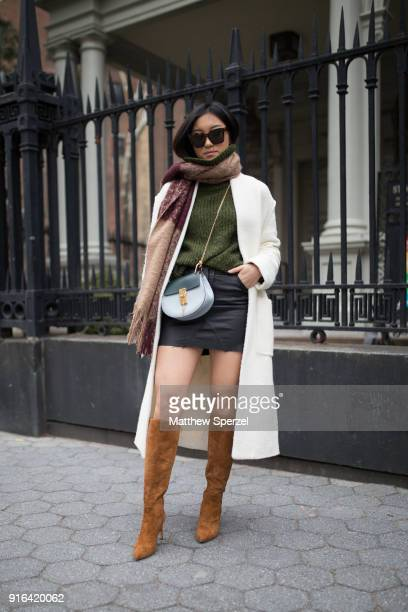 A guest is seen on the street attending Linder during New York Fashion Week wearing a white coat green sweater tan/merlot scarf and gold boots on...