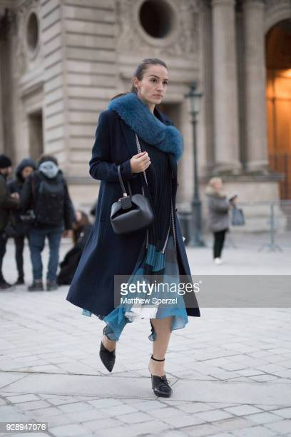 A guest is seen on the street attending Louis Vuitton during Paris Women's Fashion Week A/W 2018 wearing a long navy coat with teal fur scarf and...