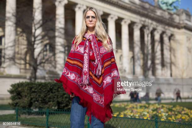 A guest is seen on the street attending Maison Margiela during Paris Fashion Week Women's A/W 2018 Collection wearing a red poncho with blue pants on...