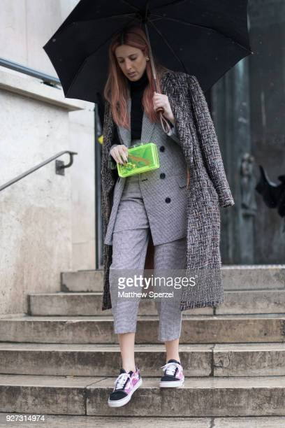 A guest is seen on the street attending Mashama during Paris Women's Fashion Week A/W 2018 wearing a tweed suit with Vans and neon green clutch on...