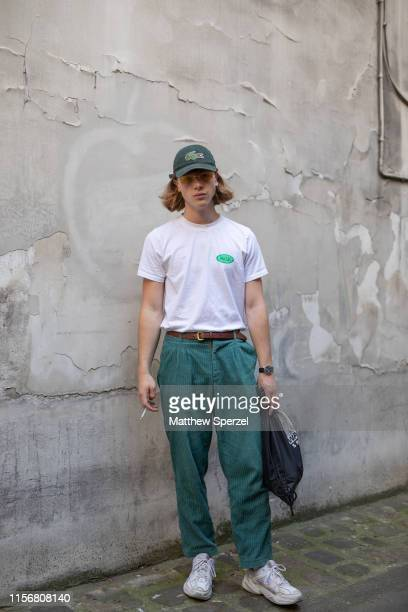 A guest is seen on the street attending Men's Paris Fashion Week wearing green slacks with Lacoste hat and white tshirt on June 18 2019 in Paris...