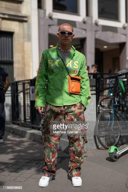 Guest is seen on the street attending Men's Paris Fashion Week wearing green/yellow track jacket, camo pants, orange cross-body bag on June 18, 2019...