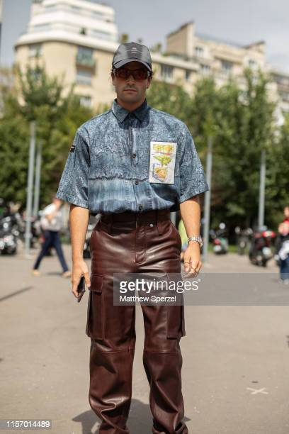 Guest is seen on the street attending Men's Paris Fashion Week wearing brown leather cargo pants with blue shirt and grey hat on June 19, 2019 in...