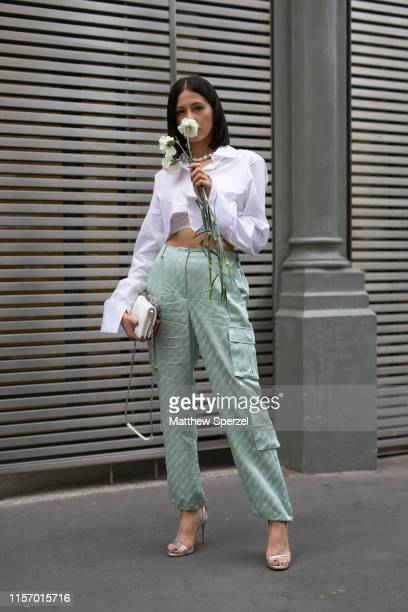 Guest is seen on the street attending Men's Paris Fashion Week wearing Off-White outfit with white top and sea green cargo pants on June 19, 2019 in...