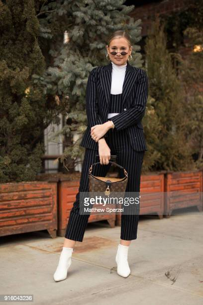 A guest is seen on the street attending Miaou during New York Fashion Week wearing a black striped suit with Louis Vuitton bag on February 8 2018 in...