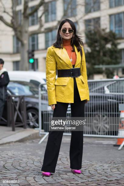 A guest is seen on the street attending Miu Miu during Paris Women's Fashion Week A/W 2018 wearing a yellow jacket with black belt and orange sweater...