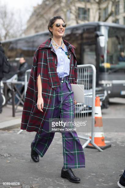 A guest is seen on the street attending Miu Miu during Paris Women's Fashion Week A/W 2018 wearing a red plaid coat purple plaid pants and blue/white...