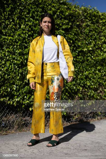 A guest is seen on the street attending NADA Miami VIP Preview during Miami Art Week wearing yellow silk suit with dark green sandals on December 6...