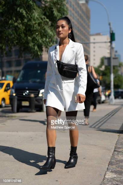 A guest is seen on the street attending New York Fashion Week SS19 wearing white blazer with black crossbody bag and boots on September 6 2018 in New...