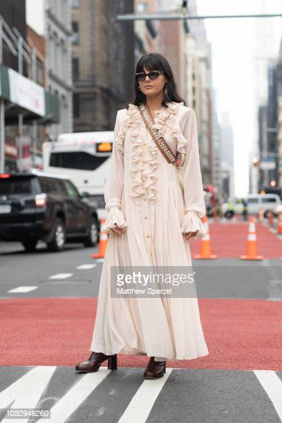 A guest is seen on the street attending New York Fashion Week SS19 wearing ruffle dress with seashell strap bag on September 12 2018 in New York City