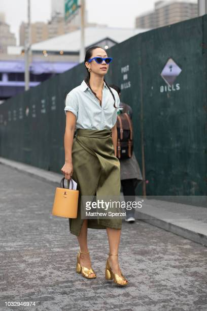 A guest is seen on the street attending New York Fashion Week SS19 wearing baby blue shirt with army green skirt and orange bucket bag on September...