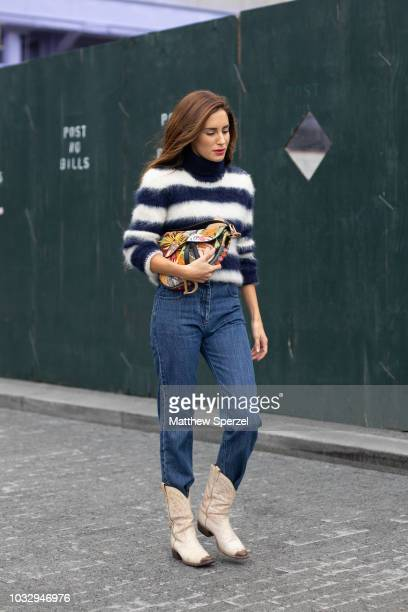 Guest is seen on the street attending New York Fashion Week SS19 wearing navy/white stripe fur sweater with blue jeans and cowgirl boots on September...