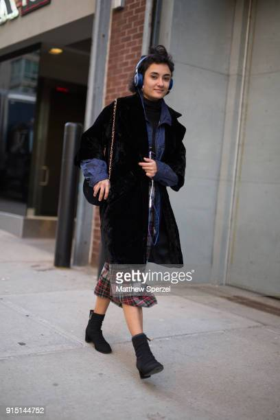A guest is seen on the street attending NHoolywood during New York Fashion Week Men's wearing a black velvet coat with denim jacket and plaid skirt...