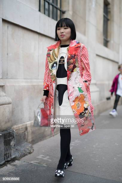 A guest is seen on the street attending Noir Kei Ninomiya during Paris Women's Fashion Week A/W 2018 wearing a multicolor floral print coat with...