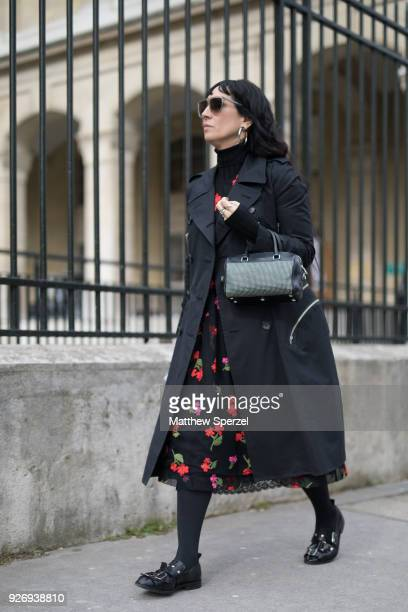 A guest is seen on the street attending Noir Kei Ninomiya during Paris Women's Fashion Week A/W 2018 wearing a black coat with black and red floral...