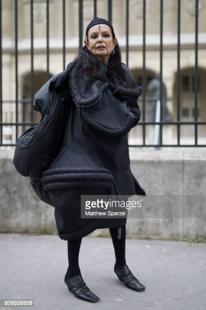 A guest is seen on the street attending Noir Kei Ninomiya during Paris Women's Fashion Week A/W 2018 wearing an avant garde black outfit with black...