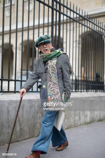 A guest is seen on the street attending Noir Kei Ninomiya during Paris Women's Fashion Week A/W 2018 wearing a grey plaid coat blue pants green plaid...