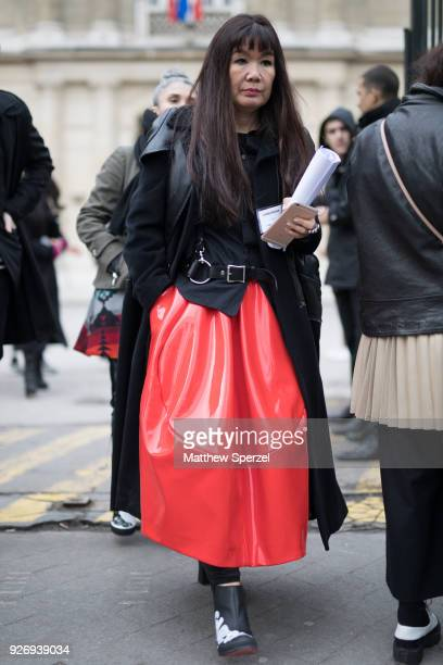 A guest is seen on the street attending Noir Kei Ninomiya during Paris Women's Fashion Week A/W 2018 wearing a black coat black leather harness and...