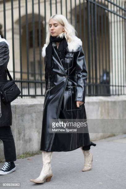 A guest is seen on the street attending Noir Kei Ninomiya during Paris Women's Fashion Week A/W 2018 wearing a long black leather coat with beige...