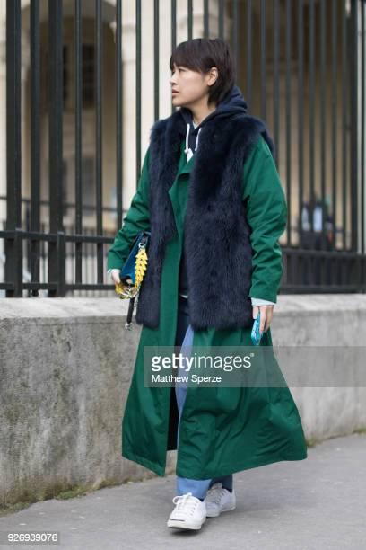 A guest is seen on the street attending Noir Kei Ninomiya during Paris Women's Fashion Week A/W 2018 wearing a long green coat with black fur vest...