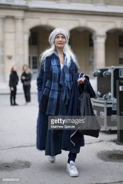 A guest is seen on the street attending Noir Kei Ninomiya during Paris Women's Fashion Week A/W 2018 wearing a long blue coat with blue plaid scarf...