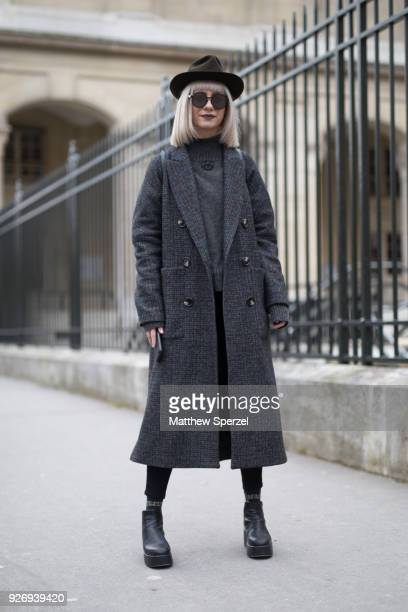 A guest is seen on the street attending Noir Kei Ninomiya during Paris Women's Fashion Week A/W 2018 wearing a grey wool coat and sweater with brown...