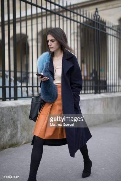 A guest is seen on the street attending Noir Kei Ninomiya during Paris Women's Fashion Week A/W 2018 wearing a black coat blue fur scarf beige top...