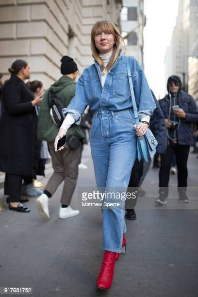 A guest is seen on the street attending OSCAR DE LA RENTA during New York Fashion Week wearing a blue denim jumpsuit with red shoes and blue bag on...
