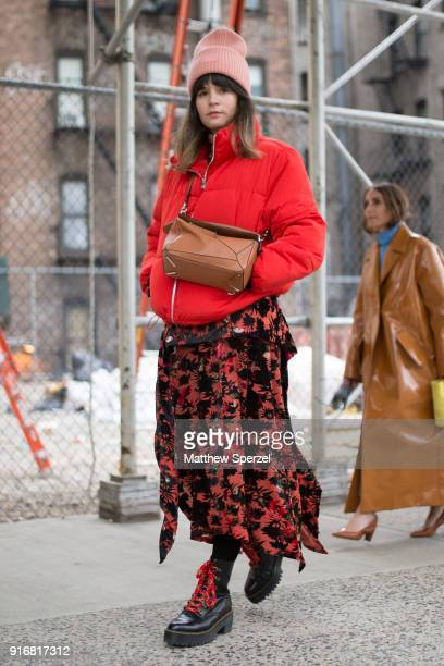 A guest is seen on the street attending R13 during New York Fashion Week wearing a red down coat with black/orange pattern dress on February 10 2018...