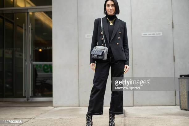 A guest is seen on the street attending Rachel Comey during New York Fashion Week wearing black blazer sweater and pants with Chanel bag and gold...
