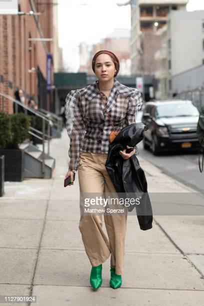 A guest is seen on the street attending Rachel Comey during New York Fashion Week wearing navy/white checker shirt brown headband and khaki pants...