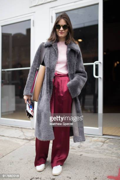 Guest is seen on the street attending Ralph Lauren during New York Fashion Week wearing a grey fur coat with burgundy satin pants and pink sweater on...
