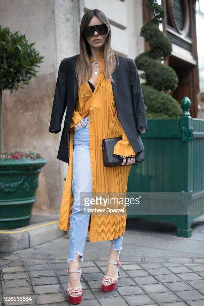 A guest is seen on the street attending Redemption during Paris Fashion Week Women's A/W 2018 Collection wearing a golden yellow outfit with torn...