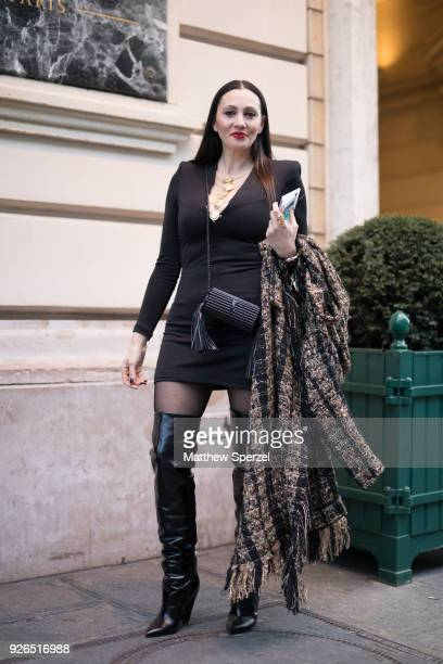 A guest is seen on the street attending Redemption during Paris Fashion Week Women's A/W 2018 Collection wearing a black dress with black thighhigh...