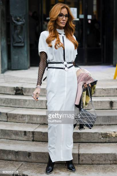 A guest is seen on the street attending Rick Owens during Paris Fashion Week Women's A/W 2018 Collection wearing a white dress black fishnet shirt...