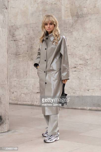A guest is seen on the street attending SACAI during Paris Fashion Week AW19 wearing grey Sacai coat on March 04 2019 in Paris France