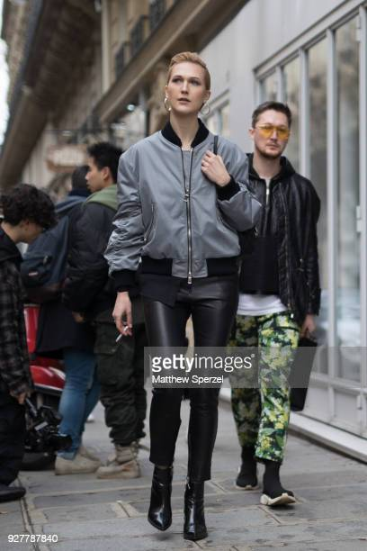 A guest is seen on the street attending Sacai during Paris Women's Fashion Week A/W 2018 wearing a grey bomber jacket on March 5 2018 in Paris France