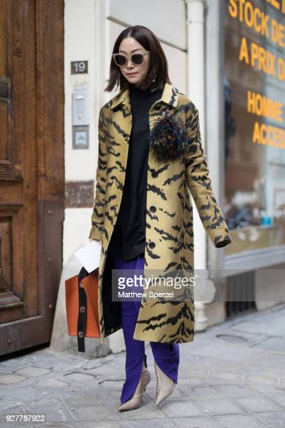 A guest is seen on the street attending Sacai during Paris Women's Fashion Week A/W 2018 wearing a animal print gold coat with purple pants and tan...