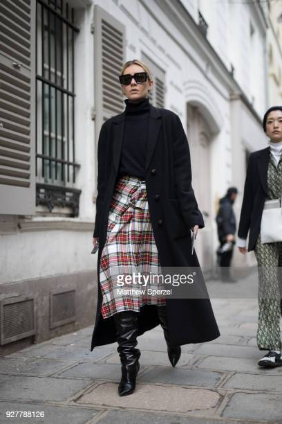 A guest is seen on the street attending Sacai during Paris Women's Fashion Week A/W 2018 wearing a plaid skirt with black turtleneck and black coat...
