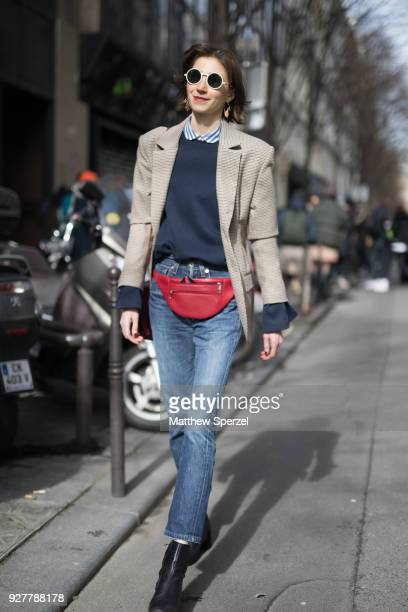 A guest is seen on the street attending Sacai during Paris Women's Fashion Week A/W 2018 wearing a taupe blazer navy sweater red hip bag and blue...