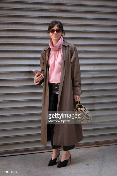A guest is seen on the street attending Sally Lapointe during New York Fashion Week wearing a long brown coat with pink sweater on February 13 2018...